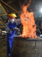 炎を上げる炉に砂鉄を投入する大原小児童