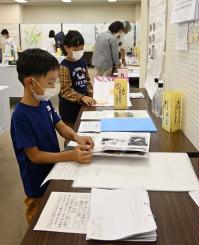 展示されている児童の研究ノートを見る子ども
