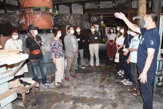 横沢孝之社長(右)の説明を受けながら月の輪酒造店の酒蔵を見学する参加者