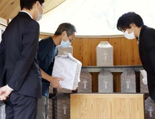 震災から9年半を経て、妻裕子さんの遺骨を受け取る三浦憲さん(中央)。左隣は長男崇さん=15日、大槌町小鎚・納骨堂