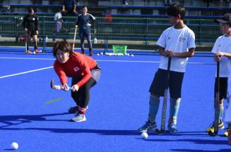 子どもたちにホッケーの基礎を指導する早野みさきさん(左)