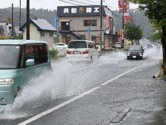 朝から降り続いた雨で冠水し車が水しぶきを上げて行き交った国道106号=23日午前8時10分、宮古市長町