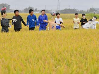かかしを設置した田んぼを訪れ、実りを実感する矢巾東小の児童=23日、矢巾町藤沢