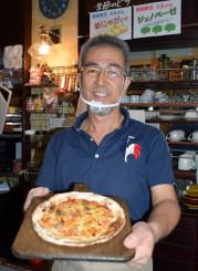 手作りピザを手に「お客さんに『また来るね』と言ってもらえる店づくりをしたい」と語る浅倉修さん