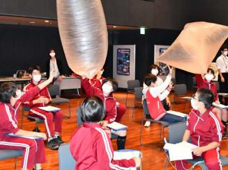 気球実験で用いられるポリエチレン製の薄膜フィルムに触れる綾里小の児童