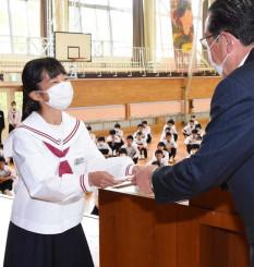 猿子恵久町長から図書カードを受け取る篠原さくらさん(左)