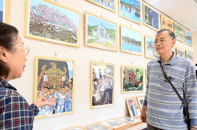 山田町の風景を切り取った作品を来場者に紹介する大川勤さん(右)