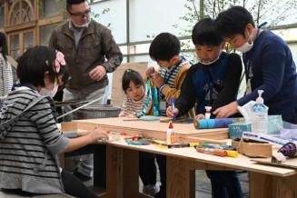斉藤健吾副会長(左奥)の指導で看板を作る児童