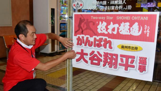 「投打猛進」と記した大谷翔平選手の応援ポスターを張り出す奥州市職員=東北新幹線水沢江刺駅