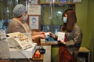 プレミアム付きチケットを使い上田商店街で飲食代を支払う岩手大生(右)。コロナ下で学生と地元商店街が連携した活性化の取り組みが注目される=盛岡市上田