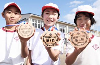 一新されたマラソン大会のメダルを手に笑顔の田頭小児童