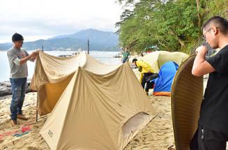 オランダ島海水浴場でテントを設営するインストラクターら