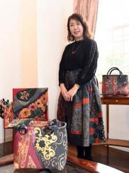 遠藤久美子さんと一閑張の椅子(左奥)やバッグ
