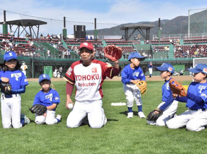 草野大輔さん(中央)から捕球のこつを教えてもらう子どもたち