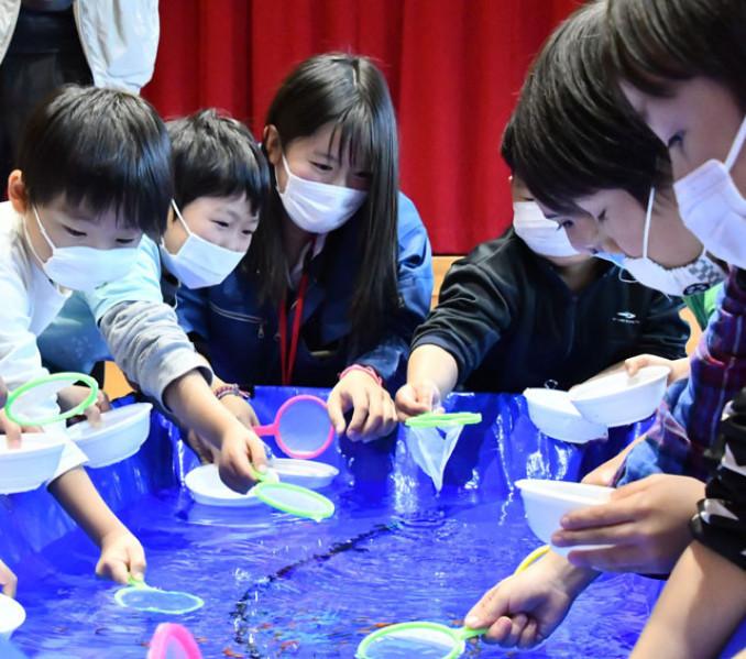 宮古水産高の生徒に教わりながら金魚すくいに挑戦する子どもら
