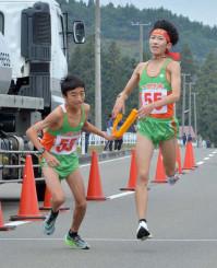 男子 一関学院の2区鈴木天智(右)が区間新の走りで首位を奪い、3区熊谷哲平にたすきをつなぐ=花巻市
