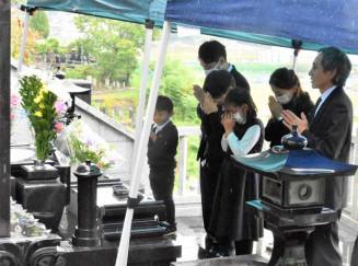 墓に遺骨を納め、手を合わせる三浦憲さん(右)と崇さん家族