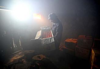 石室で甲子柿の出来栄えを確認する藤井了さん=23日、釜石市甲子町