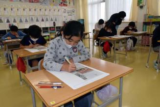 新聞記事を読み、災害が起きた時の国、県、市町村などの対応について学ぶ児童