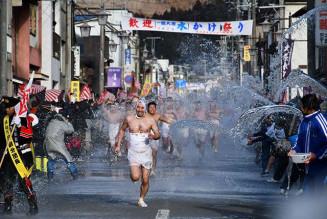 冷水を浴びて商店街を全力で駆け抜ける参加者=2月、一関市大東町大原