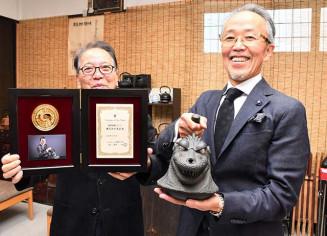 キャスティングス・オブ・ザ・イヤー賞」を受賞した南部鉄瓶ゴジラを手にする菊地章専務(右)と及川一郎社長