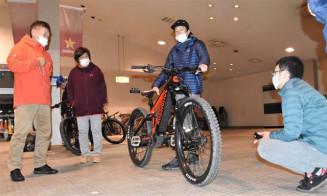 倉金純也さん(右から2人目)からイーバイクについて説明を受けるセミナー参加者
