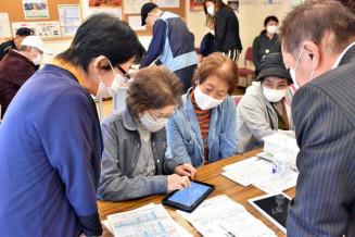 災害公営住宅の集会所でタブレット端末の操作を体験する高齢者