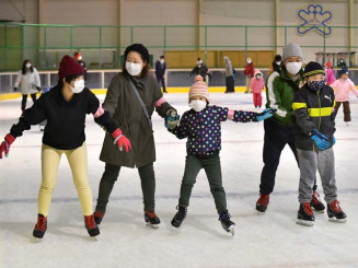 手をつないでスケートを楽しむ家族連れ