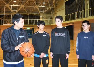 部員にシュートの打ち方を指導する大東高バスケットボール部の新井靖明監督(左)=一関市・大東高