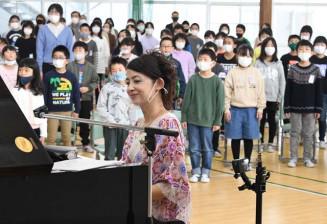 西村由紀江さん(手前)のピアノ伴奏で校歌を歌う東山小の児童