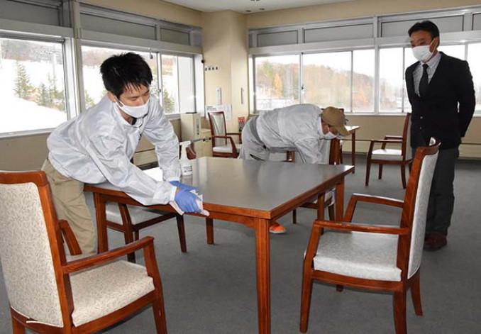 竹沢勝美支配人(右)が見守る中、テーブルに抗ウイルスの溶剤を塗る作業員
