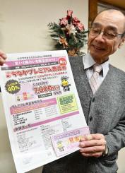 プレミアム付き商品券のチラシを手に、商店街のにぎわい回復を願う吉田建彦会長