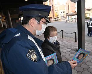 JR盛岡駅前で利用者に小原勝幸容疑者の顔写真入りチラシを配る警察官(左)