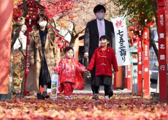 七五三参りで、紅葉を眺めながら参道を歩く家族=14日、盛岡市北山・もりおかかいうん神社