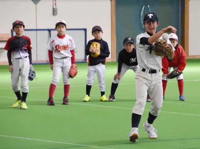 スポ少児童との守備練習で、軽快にボールをさばく平舘高の野球部員(手前)