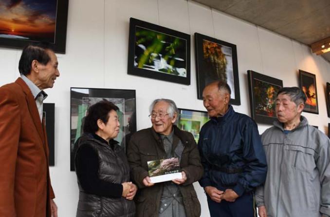 会場で写真集を手にする田村己代治さん(中央)。田頭洋子会長(左から2人目)ら関係者と意欲を燃やす