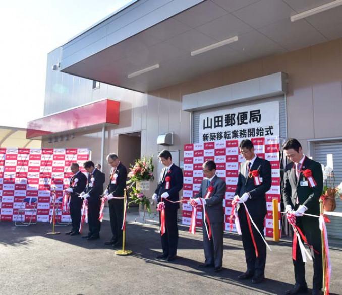 新築移転業務開始式でテープカットする山田郵便局の関係者ら