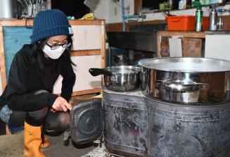 まきストーブで海水を煮詰め、塩作りに取り組む坪井奈穂美さん