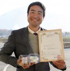 地域団体商標の登録証と八幡平マッシュルームを手に、安定供給を誓う船橋慶延理事長
