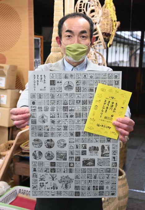完全版冊子と記念ポスターを手にする森理彦会長