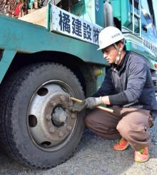 出発前にタイヤのナットに緩みがないか点検する橘建設の社員
