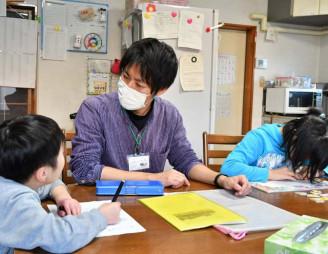 児童指導員として障害のある子どもたちと過ごす阿部類さん(中央)。正職員だが高次脳に加え経験不足もあり、まだ任されていない業務もある=盛岡市乙部