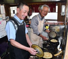 菊池英樹さん(左)にギョーザの焼き方のこつを教える夜来香の伊藤達夫オーナー=花巻市双葉町