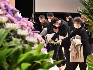 大切な人に白菊を手向け、追悼の祈りをささげる参列者=2020年3月11日、釜石市大町・釜石市民ホール