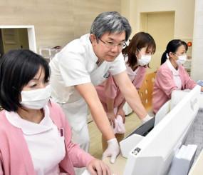 かまいしベイ眼科クリニックの開業準備に追われる佐渡一成さん(左から2人目)。古里の医療への貢献を誓う=釜石市港町