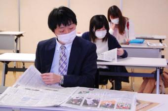 紙面に目を通し、仕事に役立ちそうな記事を探す参加者