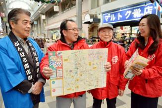 スタンプラリーのマップを手に、地元商業の活性化に期待を高める大石仁雄会長(左から2人目)ら