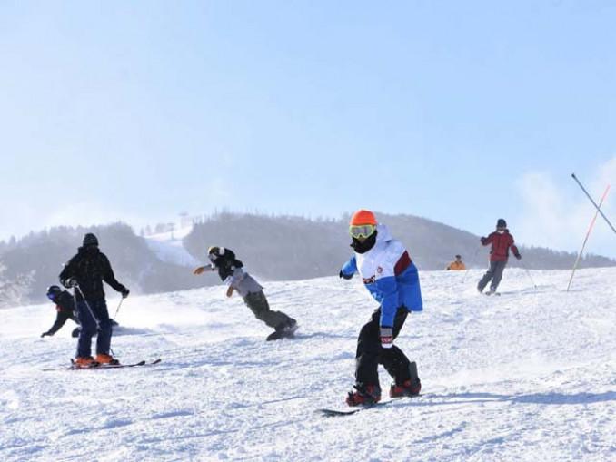 青空の下、オープン初日の雪の感触を楽しむ来場客=4日午前10時3分、八幡平市・安比高原スキー場