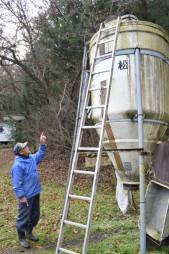 クマの入り込んだ飼料タンクを捕獲後に確認する河野隆さん=遠野市宮守町