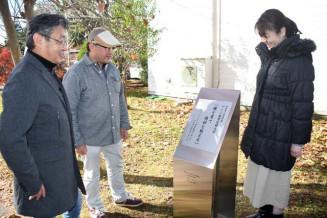 記念碑を見つめ母校への愛着をのぞかせる(左から)門間浩典さん、大石岳人さん、大石朋子さん